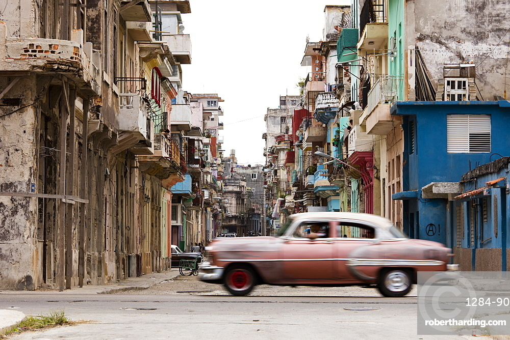 A vintage American car driving across a street in Havana, Cuba, West Indies, Caribbean, Central America