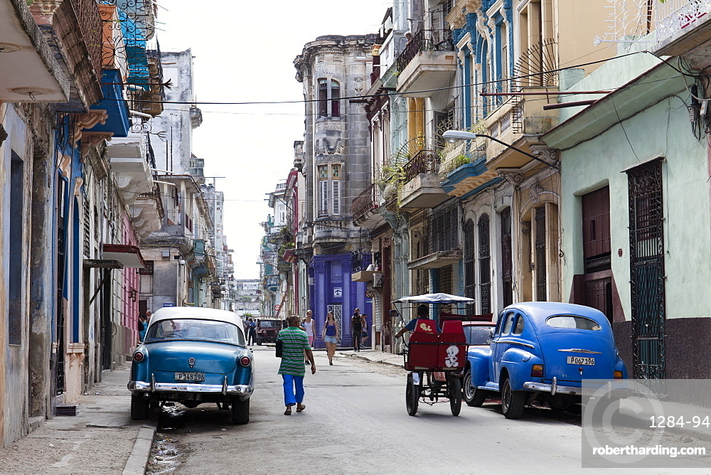 People walking past vintage American cars parked on street in Havana, Cuba, West Indies, Caribbean, Central America