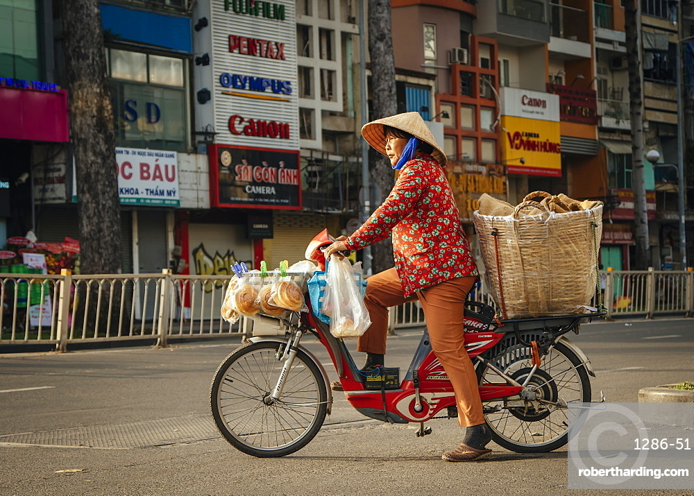Vietnamese woman on bike crossing the road