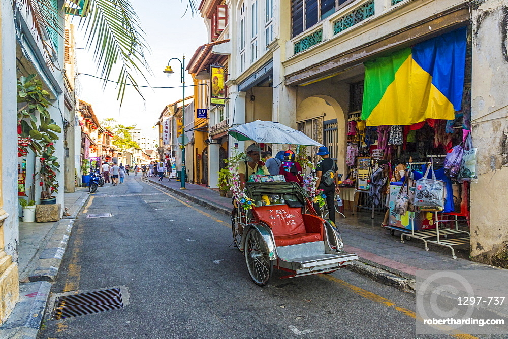 A local rickshaw tuk tuk driver in a colourful street scene in George Town, Penang Island, Malaysia, Southeast Asia, Asia.