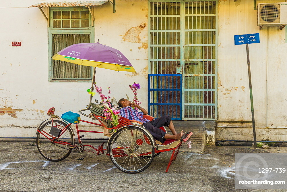 Local rickshaw tuktuk driver in George Town, Penang Island, Malaysia, Southeast Asia, Asia.