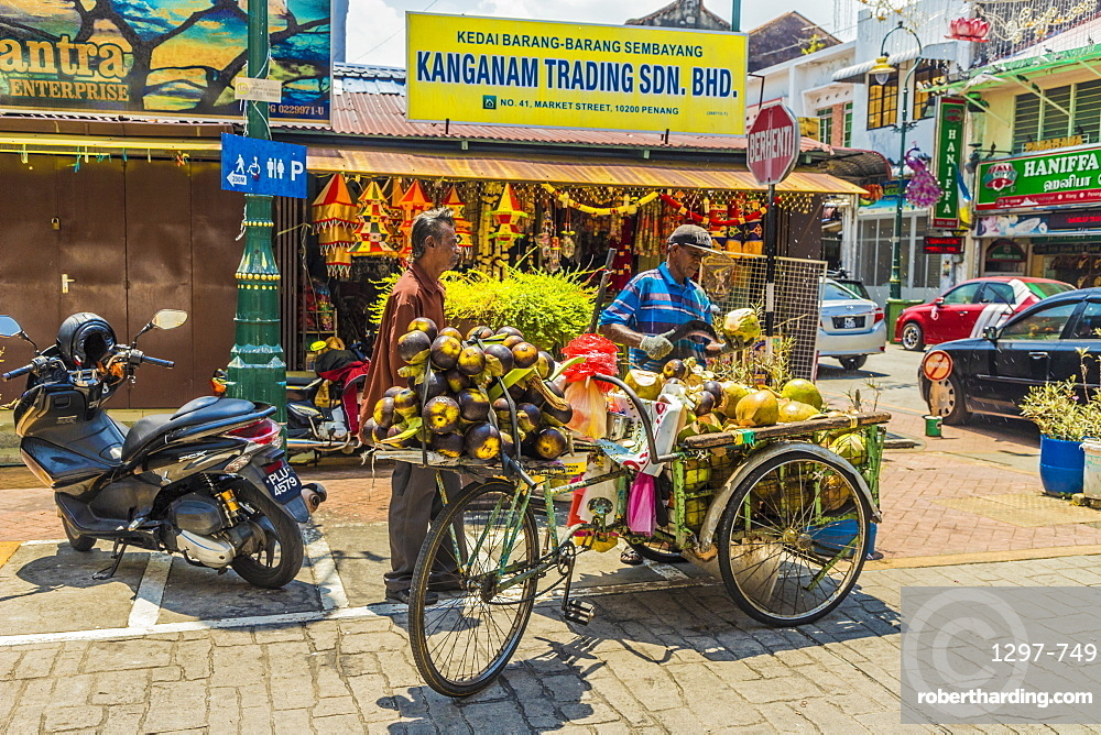A mobile coconut seller and his stall in Little India, George town, Penang Island, Malaysia, Southeast Asia, Asia.
