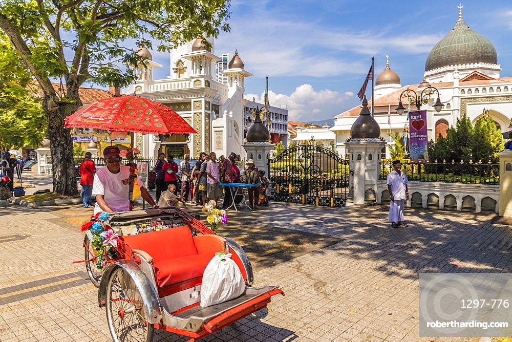 A local rickshaw tuk tuk outside Kapitan Keling Mosque, in George Town, Penang Island, Malaysia, Southeast Asia, Asia.