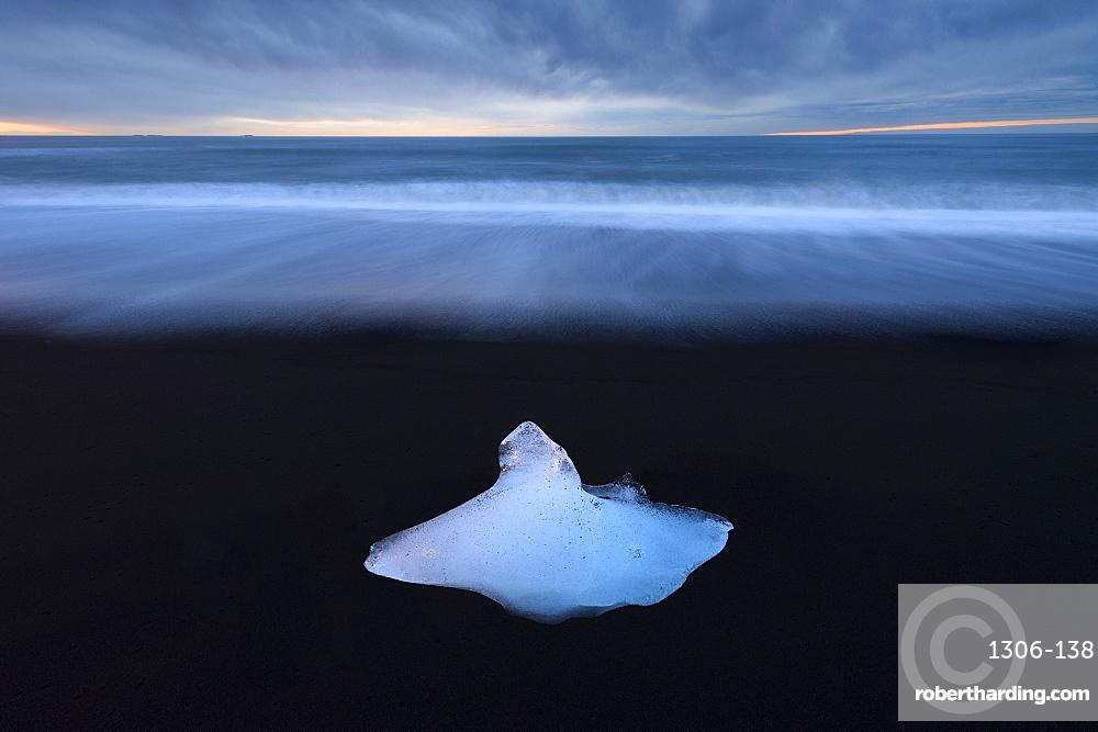 Glacier ice on black sand beach with waves washing up the beach, near Jokulsarlon, South Iceland, Iceland, Polar Regions