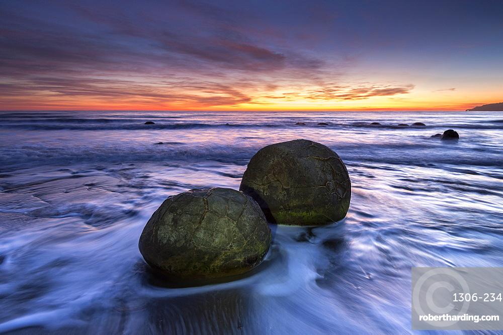 The Moeraki Boulders with dramatic sunrise at Moeraki Beach, Otago, New Zealand