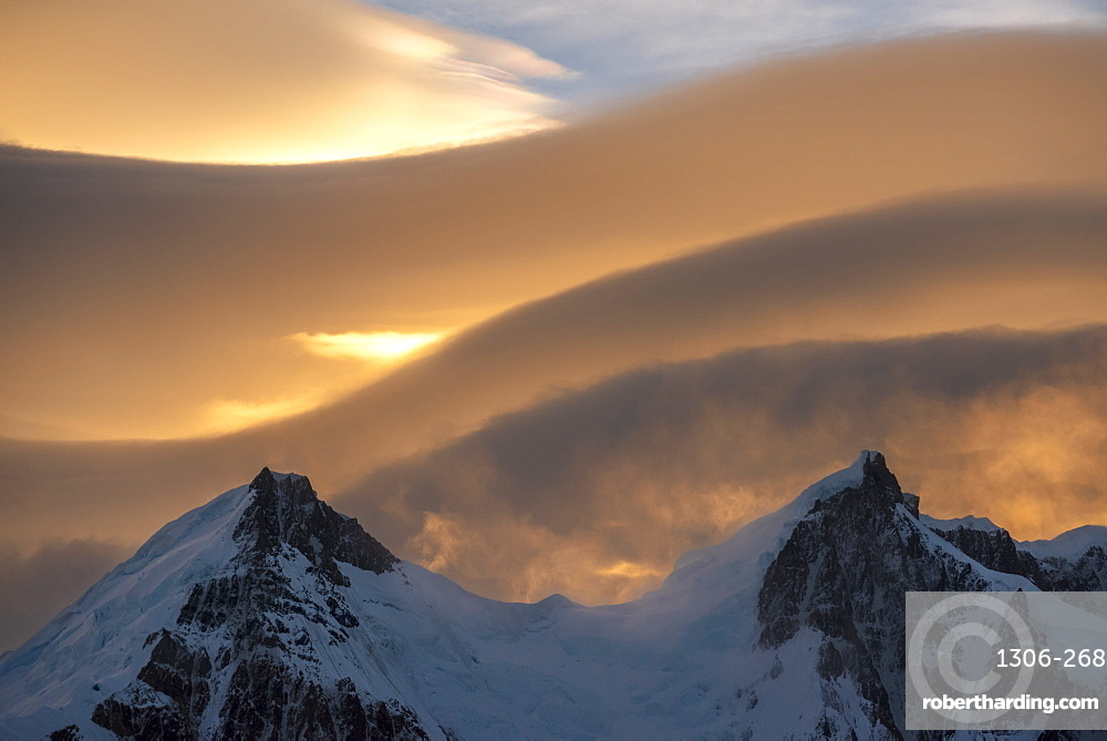 Lenticular clouds above snow covered mountain range, El Chalten