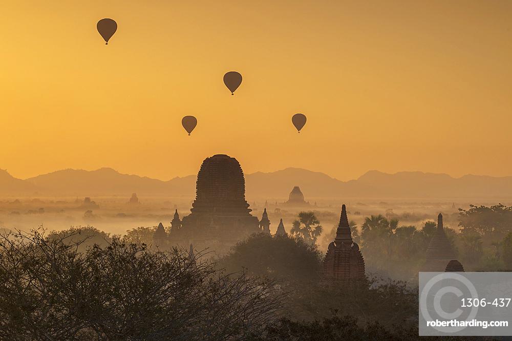 Atmospheric sunrise with ballons over Stupas in Bagan, Bagan, Myanmar