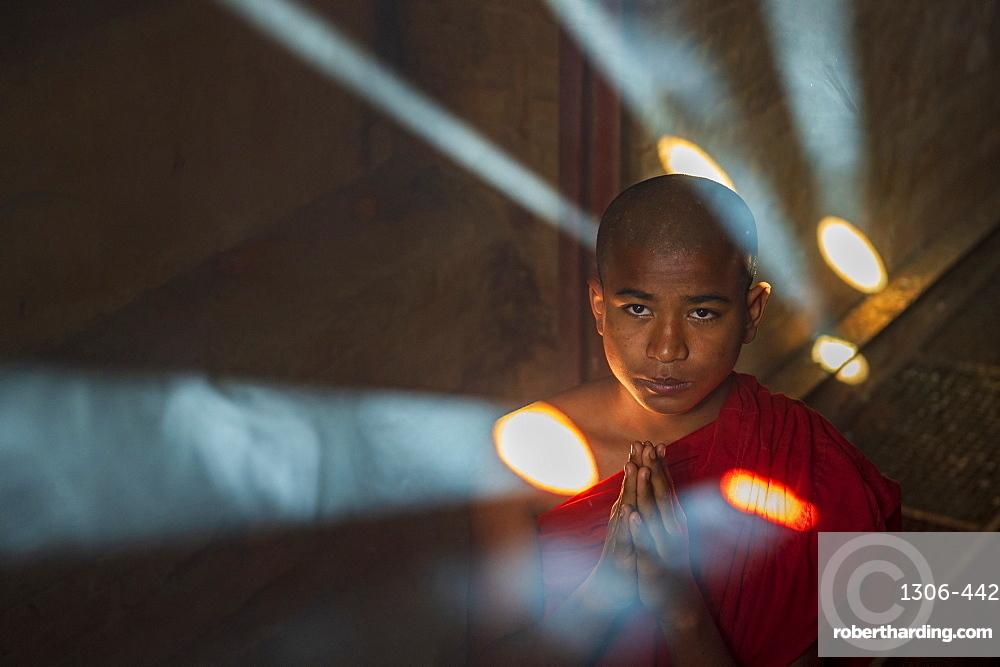 Novice monk praying with shafts of light, Bagan, Myanmar