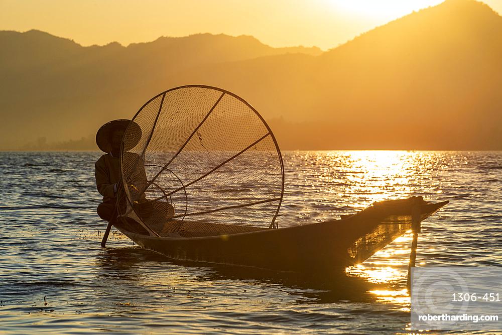 Intha leg rowing fisherman at sunset on Inle Lake, Shan State, Myanmar
