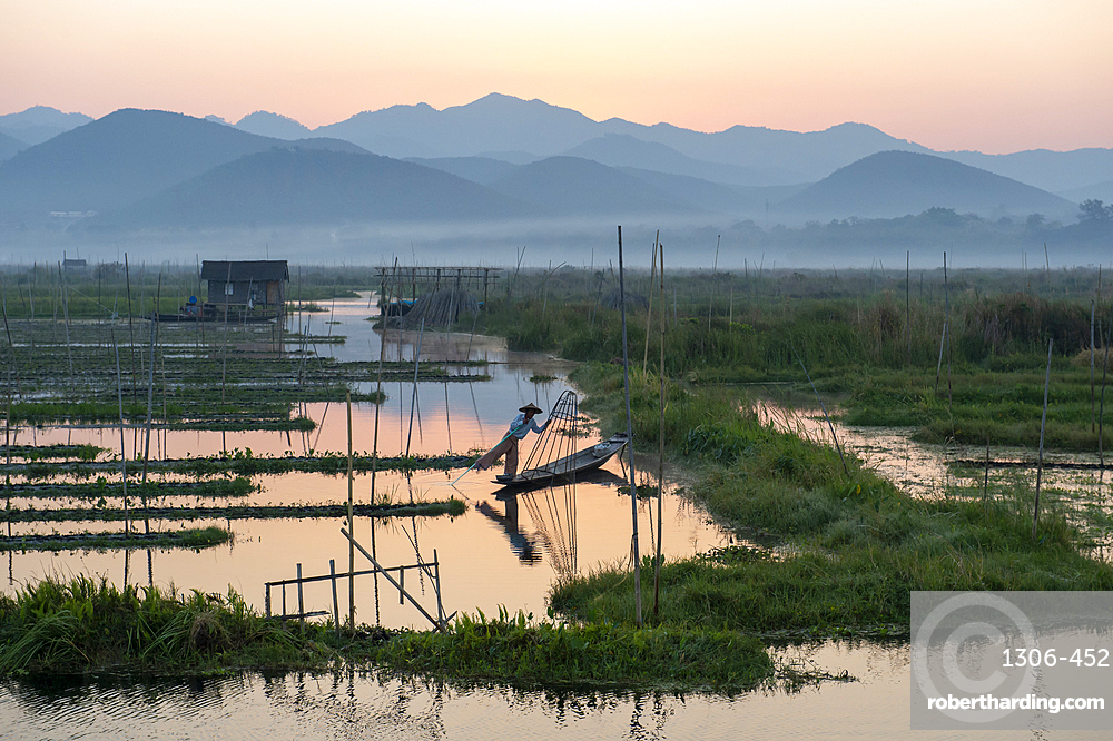 Intha leg rowing fisherman stood with net at Inle Lake gardens backed by mountains, Inle Lake, Shan State, Myanmar.