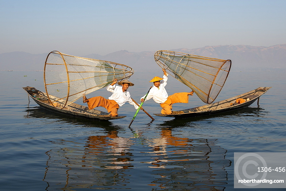 Two Intha leg rowing fisherman holding up fishing nets, Inle Lake., Shan State, Myanmar