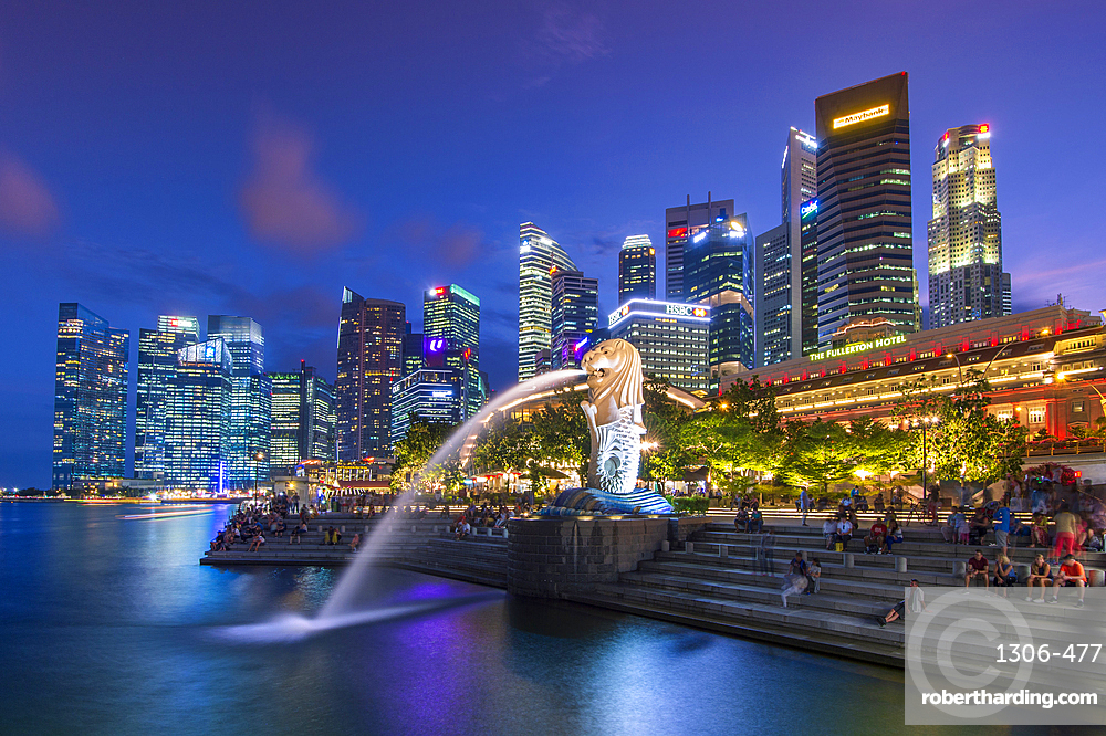The Merlion at Marina Bay with The Fullerton Hotel set against The Financial District at night, Singapore