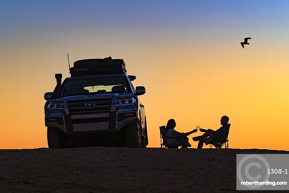 Couple toasting a sunset next to their off-road vehicle, Dampier, Western Australia, Australia, Pacific