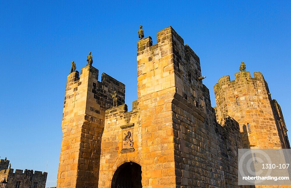 The medieval barbican and gatehouse of Alnwick Castle, sunset, Alnwick, Northumberland, England, UK