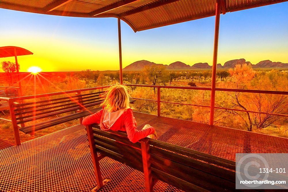 Tourist woman sitting on a bench at platform dune viewing area and looking Mount Olga in Uluru-Kata Tjuta National Park at orange sunset sky. Australian outback in Northern Territory, Australia