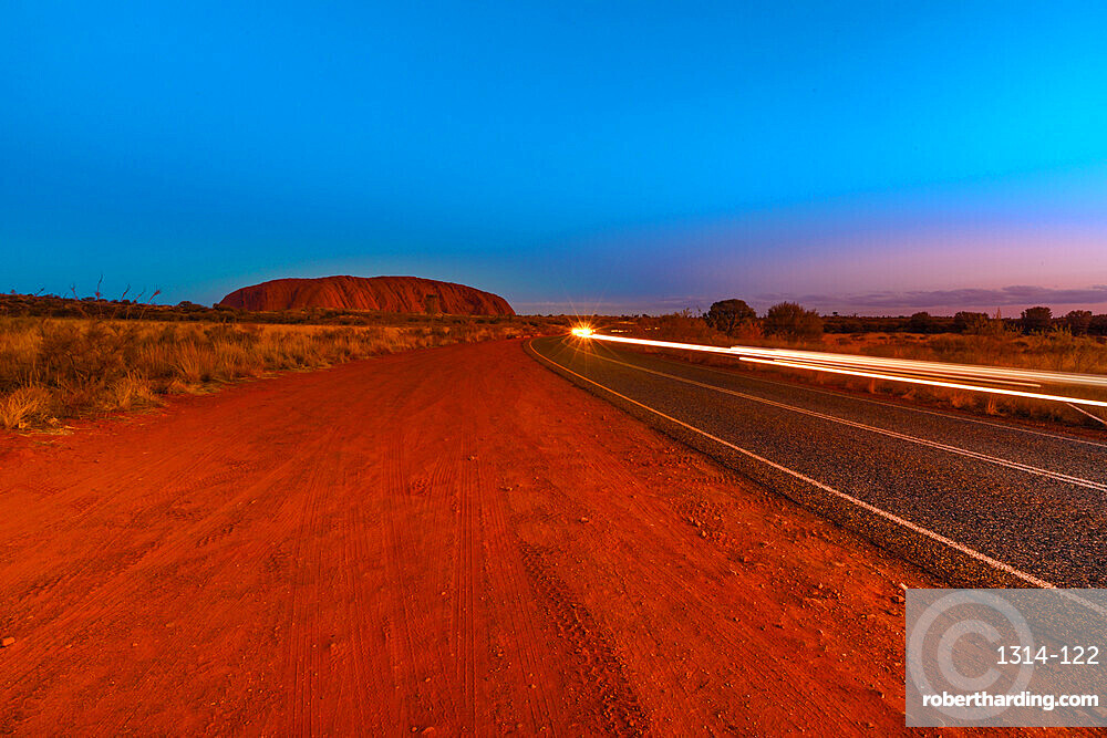 Car light trails along the road to Uluru Ayers Rock at night. The huge sandstone monolith icon of Australian outback Red Centre in Uluru-Kata Tjuta National Park. Central Australia, Northern Territory