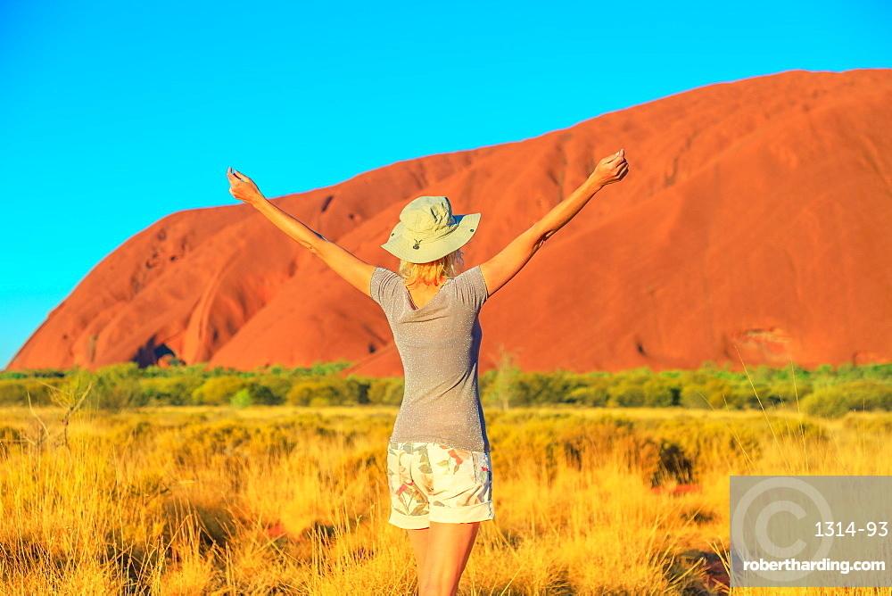 Carefree tourist woman with raised arms enjoys Uluru Ayers Rock at sunset in Uluru-Kata Tjuta National Park. Blonde traveler in Australian outback Red Centre. Tourism in Northern Territory, Australia.