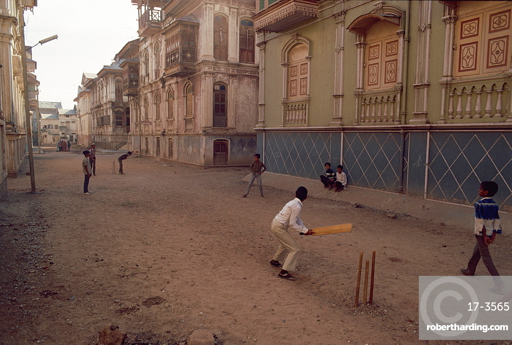 Children play cricket in the street, Sidpur, India, Asia