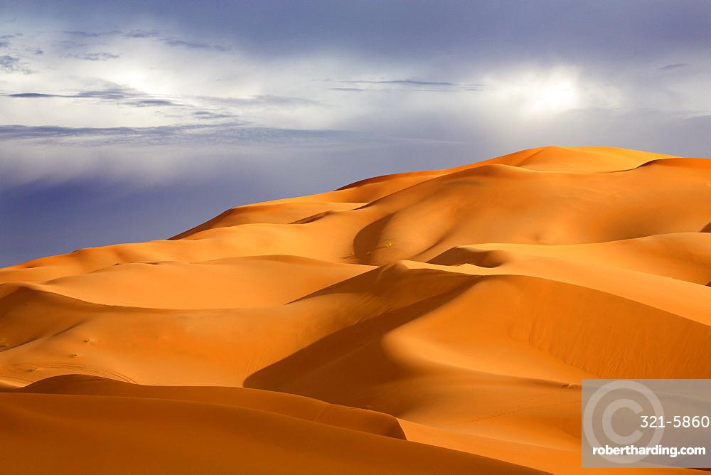 Orange sand dunes against stormy sky, Erg Chebbi sand sea, part of the Sahara Desert near Merzouga, Morocco, North Africa, Africa