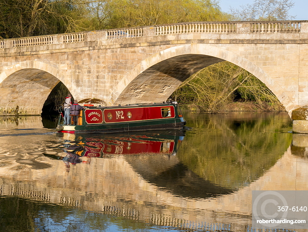 Red narrow boat passes under Shillingford Bridge reflected in River Thames, Shillingford, Oxfordshire, England, United Kingdom, Europe