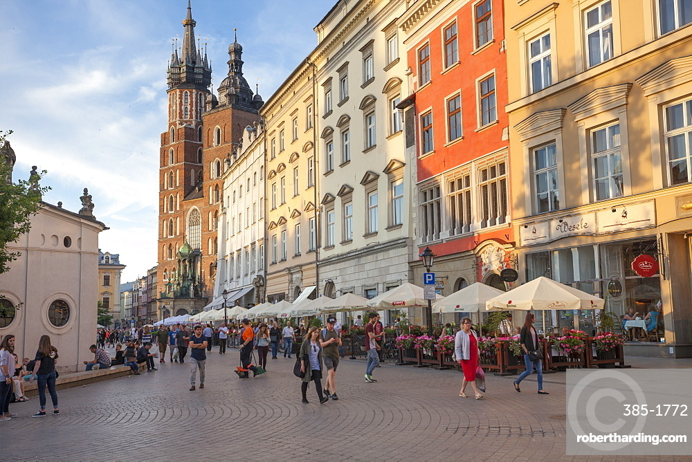 Cafes line the old town centre of Rynek Glowny (Main Square), with St. Mary's Basillica in background, Old Town, UNESCO World Heritage Site, Krakow, Poland, Europe