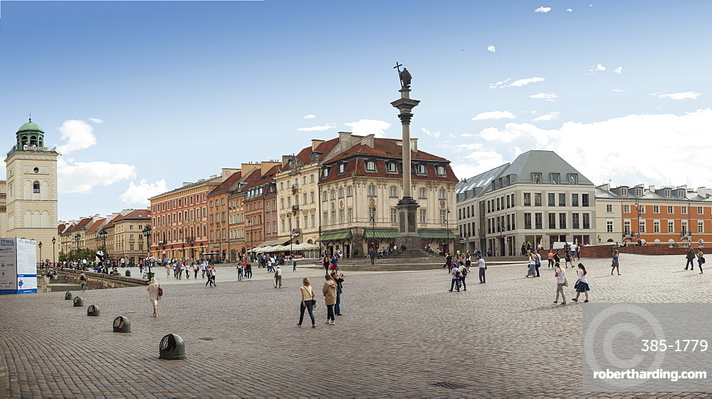 Tourists walk across Castle Square Plac Zamkowy, site of Sigismund's Column and Royal Castle - UNESCO old town rebuilt after WW2