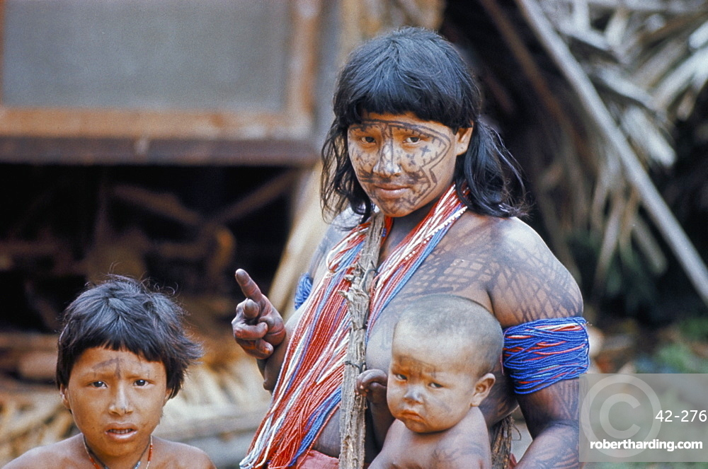 Heavily painted Tirio Indian woman wearing beads, with children, Brazil, South America