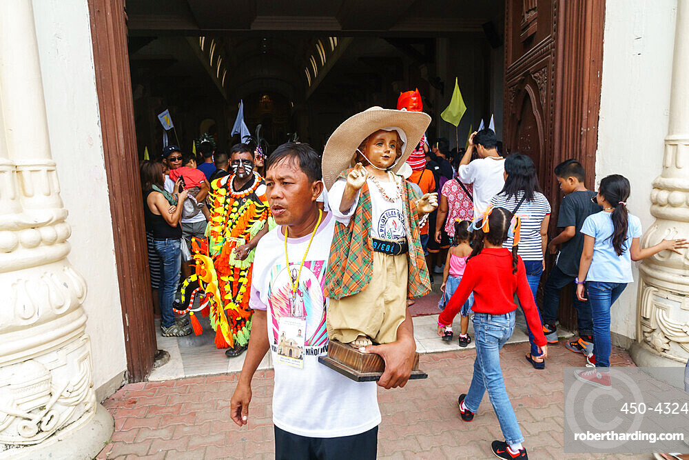 Worshipper at the door of the Cathedral with Baby Jesus statuette at the annual Ati-Atihan Festival, Kalibo Island, Philippines
