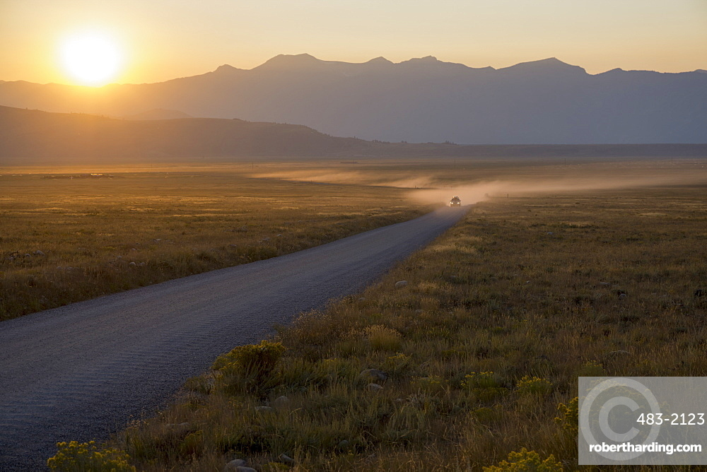 Car on dusty road at sunset, Grand Teton Park, Wyoming, United States of America, North America