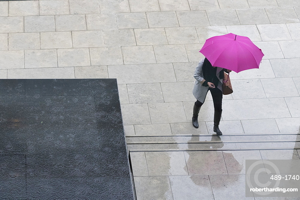 Woman with umbrella and mobile phone walking up steps to Auckland Art Gallery, Auckland, North Island, New Zealand, Pacific