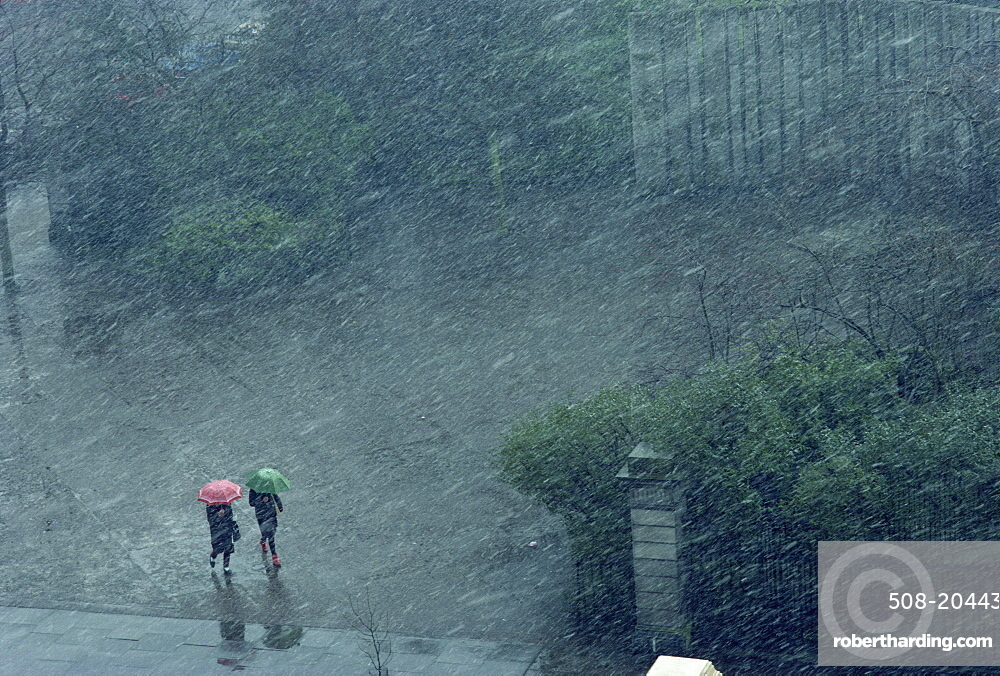 Two lone figures with umbrellas caught in rain storm, Dublin, Republic of Ireland, Europe