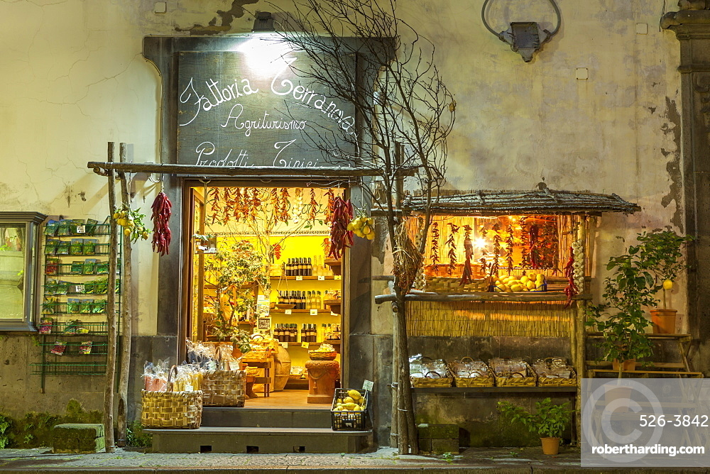 Shop lit up selling produce at night in the back streets of Sorrento, Campania, Italy, Europe