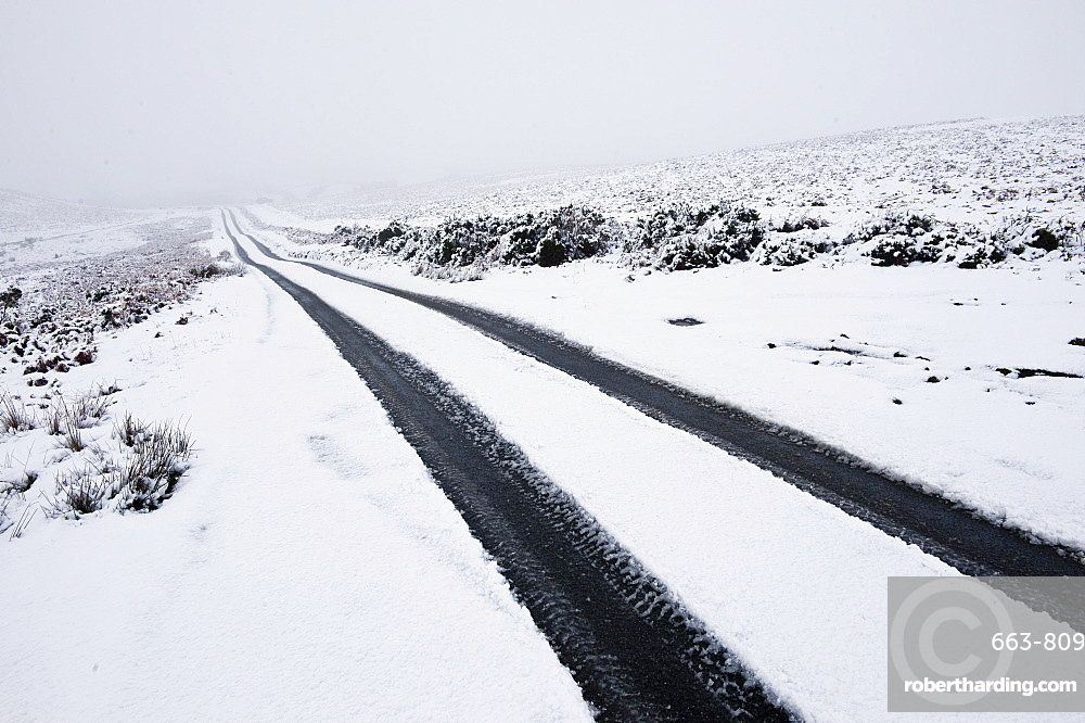 Car tyre tracks on a snowy road on the Mynydd Epynt moorland, Powys, Wales, United Kingdom, Europe