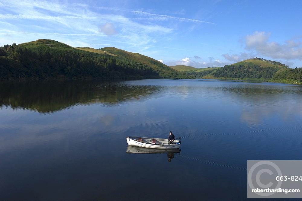A man fishing from a boat at Llyn (Lake) Clywedog, Llanidloes, Powys, Wales, United Kingdom, Europe