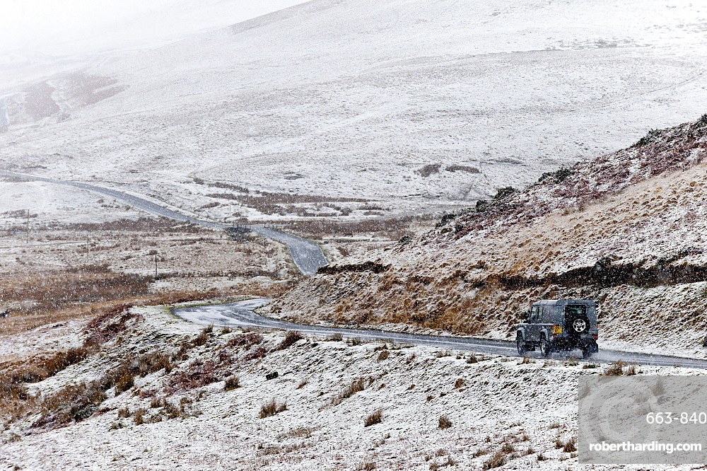 A four wheel drive vehicle negotiates a road through a wintry landscape in the Elan Valley area in Powys, Wales, United Kingdom, Europe