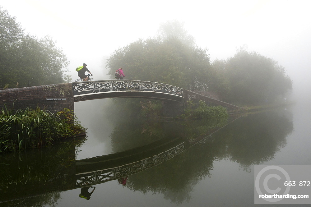 A cyclist on a bridge on Birmingham Canal Navigations (BCN), Birmingham, West Midlands, England, United Kingdom, Europe