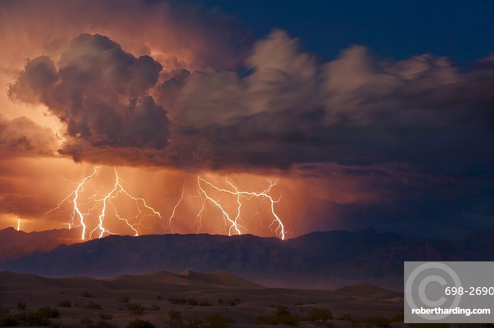 Electrical storm with forked lightning over the Grapevine mountains of the Amargosa Range, Mesquite Flats Sand dunes in the valley, Stovepipe Wells, Death Valley National Park, California, United States of America, North America