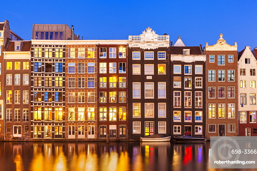 Dutch gables on row of typical Amsterdam houses at night with reflections in the Damrak canal, Amsterdam, North Holland, Netherlands, Europe