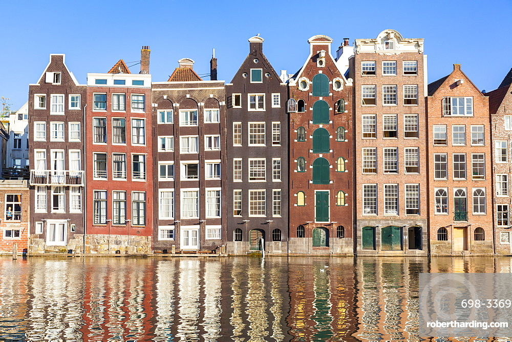 Dutch gables on a row of typical Amsterdam houses with reflections, Damrak Canal, Amsterdam, North Holland, Netherlands, Europe