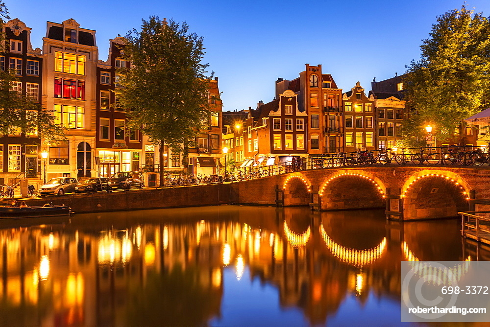 Illuminated canal bridge with reflections at night over the Singel Torensluis canal, Amsterdam, North Holland, Netherlands, Europe