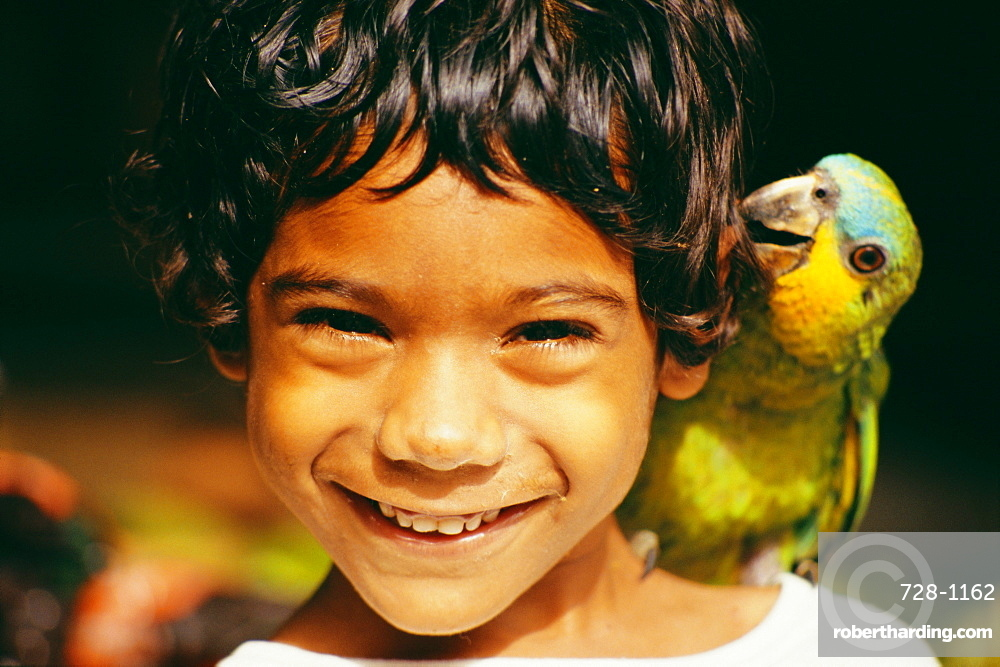 Head and shoulders portrait of a young boy with pet parrot, West Indies, Caribbean, Central America