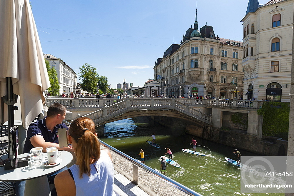 A bar overlooking the Triple Bridge over the Ljubljanica River, Ljubljana, Slovenia, Europe