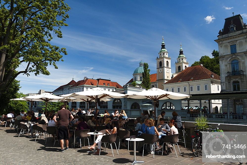 Outdoor cafes along the Ljubljanica river and the Cathedral of Saint Nicholas in the background, Ljubljana, Slovenia, Europe