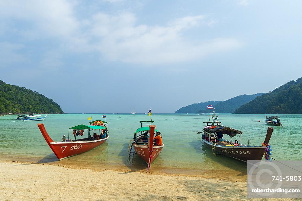 Three long tailed boats on a sandy beach.