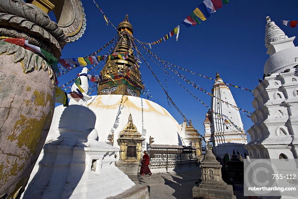 A monk walks clockwise around the buddhist stupa called Swayambhu or Swayambhunath, Kathmandu, Nepal