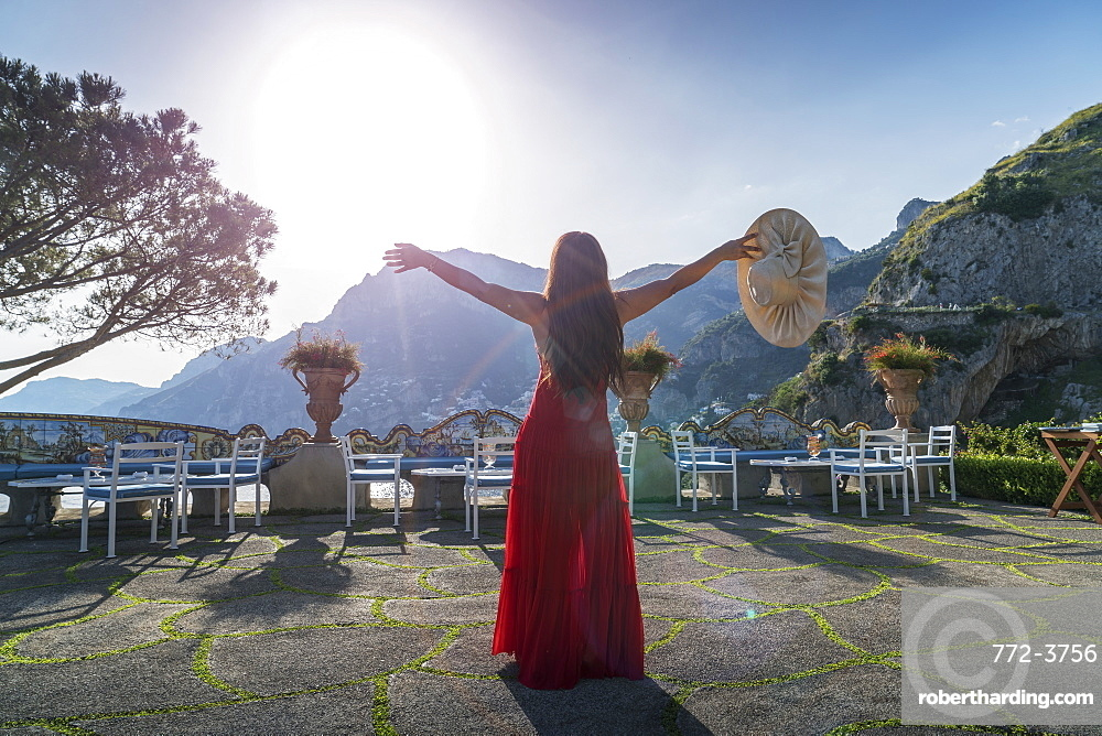 Woman with red dress on the Amalfi Coast, Italy.