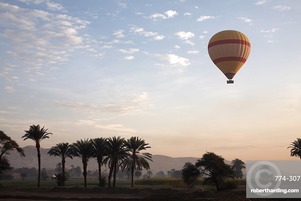Hot air balloons carry tourists on early morning flights over the Valley of the Kings, Luxor, Egypt, North Africa, Africa