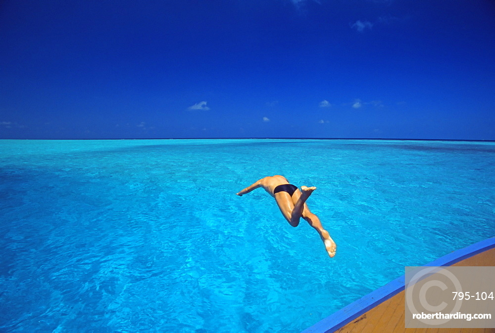 Man jumping into tropical sea from deck, Maldives, Indian Ocean, Asia