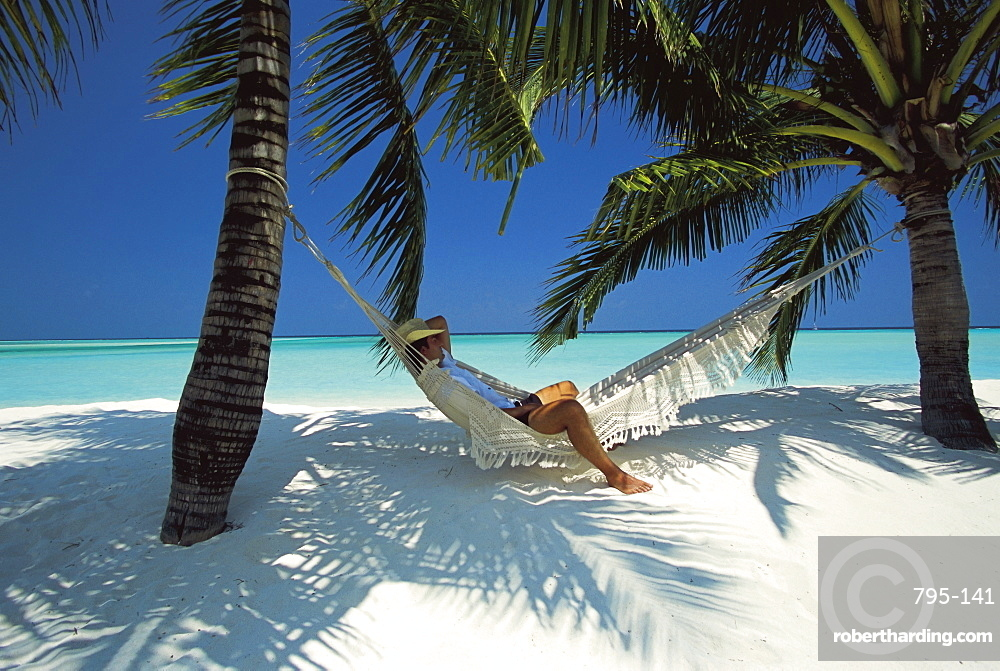 Man relaxing on a beachside hammock, Maldives, Indian Ocean, Asia
