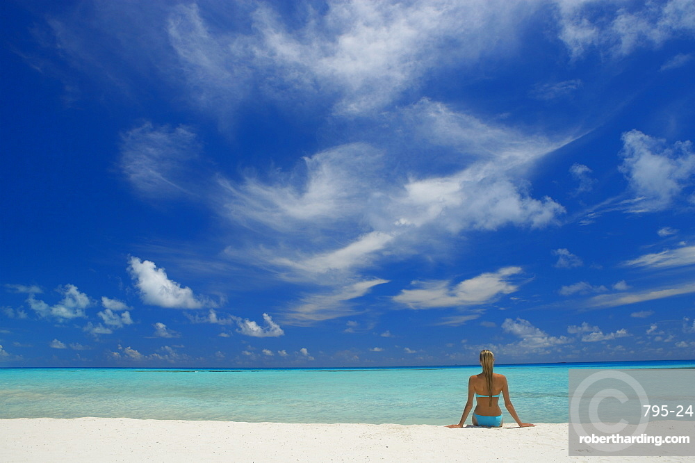 Woman sitting on the beach looking out to sea, Maldives, Indian Ocean, Asia
